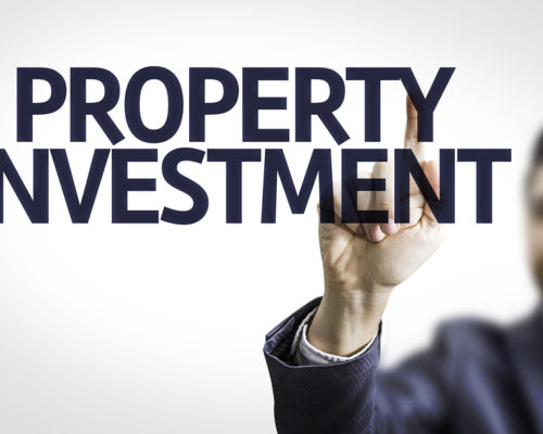 Business man pointing to transparent board with text: Property Investment