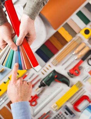 Male hands holding swatches and choosing the right color work tools on background top view DIY and home renovation concept